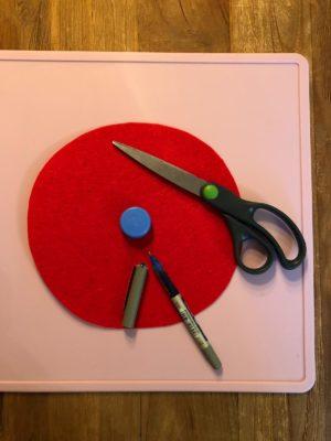 Loch aus rotem Filz-Kreis ausschneiden